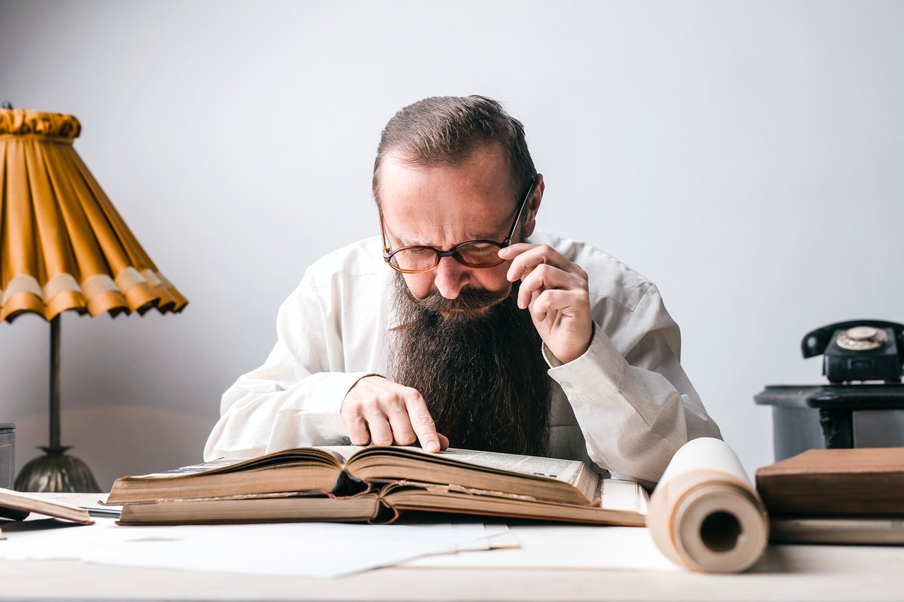 Old bearded man reading a book